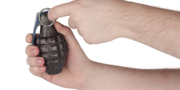 Hands holding grenade pulling the pin.Please also see: