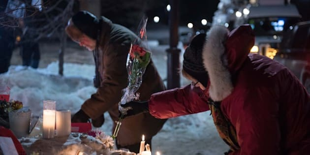 People place candles near a mosque that was the location of a shooting spree in Quebec City, Quebec on January 31, 2017.
