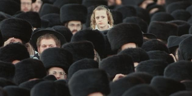 JERUSALEM:An ultra-orthodox Jewish boy is lifted up over a crowd of tens of thousands of Hassidim gathered in Jerusalem 01 December for the wedding of Yisrael Menahem, the son of the Rabbi of Gur, to Esther, the granddaughter of the Rabbi of Lublin.  The wedding, one of the biggest in recent memory, hosted thousands of followers, with meals served to some ten thousand people. (Photo credit should read MENAHEM KAHANA/AFP/Getty Images)