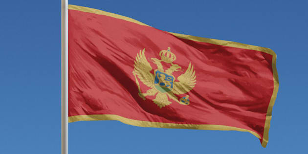 Flag of Montenegro in front of a clear blue sky