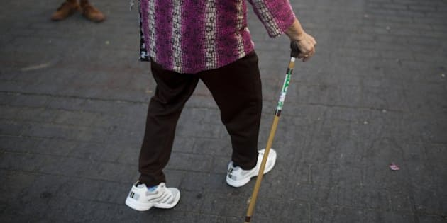 A woman uses a walking cane as she walks at Lumphini Park in Bangkok, Thailand, on Sunday, March 15, 2015. Almost a third of Thailand's population will be over 60 by 2050, according to the United Nations. That puts the country at a disadvantage among the Association of Southeast Asian Nations just as rising costs in China are pushing manufacturers to find new bases in the region. Photographer: Brent Lewin/Bloomberg via Getty Images