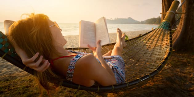 Young lady reading a book in hammock on a beach at sunset