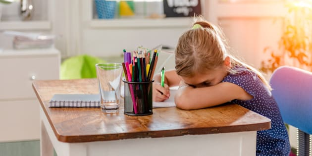 Girl in blue shirt having problem with concentration to finish home work