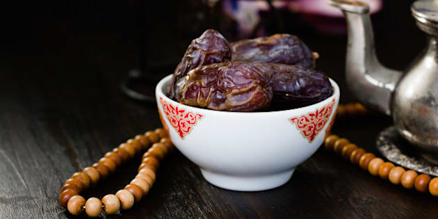 Ramadan fasting - dates for iftar in bowl on wooden table