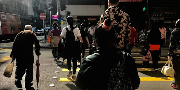 A man casts a shadow as he uses an umbrella to lean on while crossing a road with other pedestrians in Hong Kong, China, December 12, 2016. Picture taken December 12, 2016.      REUTERS/David Gray