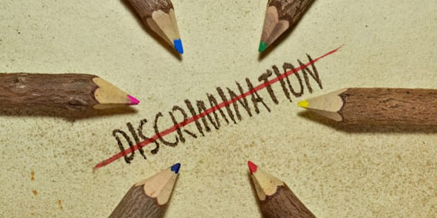 Conceptual image with pencils on vintage background to stop discrimination. Six handcrafted wooden pencils arranged in a circle and the word Discrimination with red line in the middle.