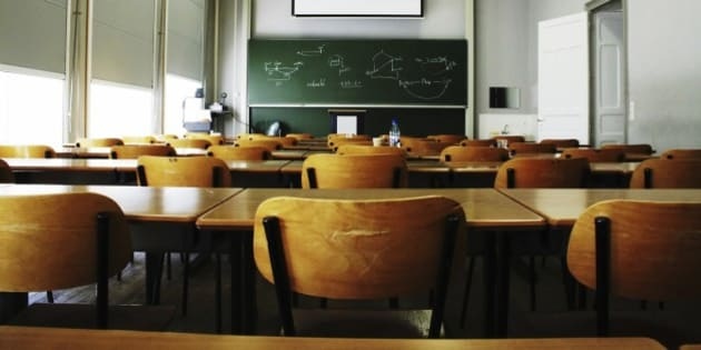 A large, empty classroom, lit by morning light.