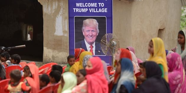 Indian women gather to listen to a speaker next to a poster with the image of  US President Donald Trump during a ceremony at Marora village, which has been unofficially renamed 'Trump Village,' about 100km from New Delhi, on June 23, 2017. A rural Indian settlement with little electricity or running water renamed itself 'Trump Village' on June 23 in an unusual gesture to the American president ahead of Prime Minister Narendra Modi's trip to Washington. A huge billboard declaring 'Welcome to Trump Village' in Hindi and English, accompanied with a beaming portrait of the US president, was unveiled in Haryana state's Marora, as the village is officially known. The water and sanitation group Sulabh, which has been installing toilets in the impoverished settlement, suggested the name change to the local council.  / AFP PHOTO / MONEY SHARMA        (Photo credit should read MONEY SHARMA/AFP/Getty Images)