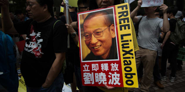 Radical legislator ÒLong HairÓ Leung Kwok-hung holds a banner of Chinese dissident Liu Xiaobo during a pro-democracy protest in Hong Kong on May 18, 2016, during the second day of a visit by China's National People's Congress (NPC) Standing Committee Chairman Zhang Dejiang. One of China's most powerful officials arrived in Hong Kong on May 17 in an attempt to build bridges in the divided city, but the trip has already stirred anger among opponents.  / AFP / DALE DE LA REY        (Photo credit should read DALE DE LA REY/AFP/Getty Images)
