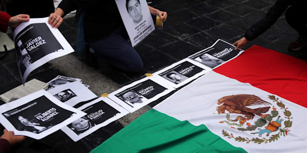 People place photos of murdered journalists next to the national Mexican flag during a demonstration against the killing of journalists in Mexico and to demand justice for the 43 missing students of Ayotzinapa Rural Teachers' College outside Argentina's Foreign Ministry in Buenos Aires, Argentina, May 24, 2017. REUTERS/Marcos Brindicci