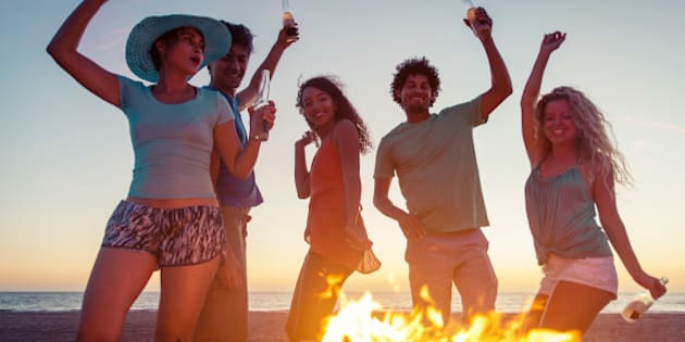 Group of friends making party on the beach with fire and music
