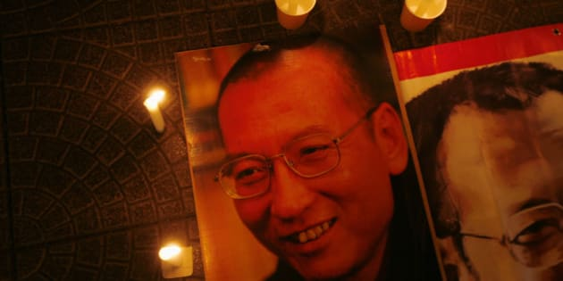Candles are placed around portraits of jailed Chinese pro-democracy activist Liu Xiaobo during a candlelight vigil demanding his release, outside the Legislative Council in Hong Kong November 2, 2010. It is unclear who will accept the Nobel Peace Prize awarded to jailed Chinese dissident Liu Xiaobo and the Norwegian Nobel Committee may keep custody of it for the time being, its secretary said last week. REUTERS/Bobby Yip   (CHINA - Tags: POLITICS CIVIL UNREST)
