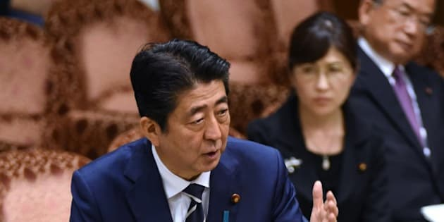 Japan's Prime Minister Shinzo Abe (L) answers questions during a budget dommittee meeting in the Upper House at parliament in Tokyo on July 25, 2017, as he and other relevant ministers were expected to face more questioning over issues over a suspected scandal.