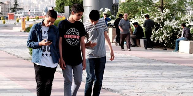 Iranian youth use their mobile phones as they walk at a park in Tehran, Iran, May 16, 2017. REUTERS/TIMA ATTENTION EDITORS - THIS IMAGE WAS PROVIDED BY A THIRD PARTY. FOR EDITORIAL USE ONLY.