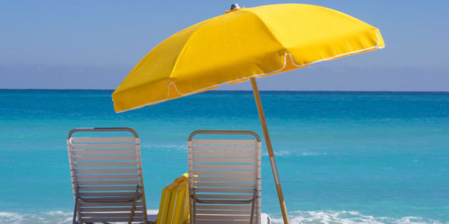 'Yellow Beach umbrella and deck chairs on the beach on a clear day on South beach, Miami'
