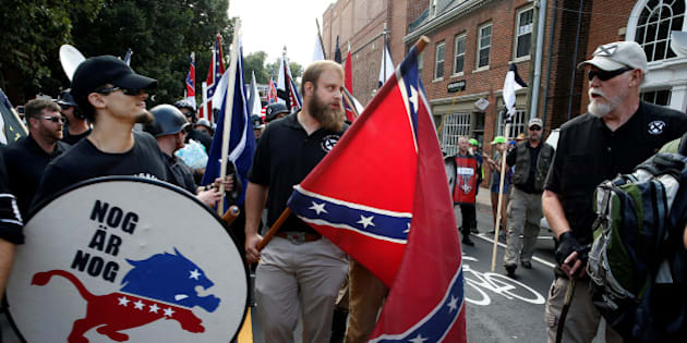 White supremacists carry a shield and Confederate flag as they arrive at a rally in Charlottesville, Virginia, U.S., August 12, 2017.   REUTERS/Joshua Roberts