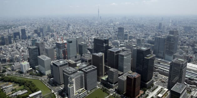Commercial buildings, bottom, stand in the Marunouchi and Otemachi districts in this aerial photograph taken in Tokyo, Japan, on Wednesday, June 24, 2015. The Abe administration aims to cap increases in spending as it tries to rein in the world's heaviest debt load while sustaining a recovery from two decades of stagnation. Photographer: Kiyoshi Ota/Bloomberg via Getty Images