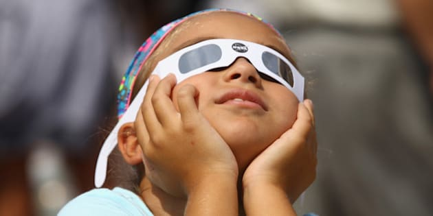GARDEN CITY, NY - AUGUST 21:  A spectator looks skyward during a partial eclipse of the sun on August 21, 2017 at the Cradle of Aviation Museum in Garden City, New York. Millions of people have flocked to areas of the U.S. that are in the 'path of totality' in order to experience a total solar eclipse. During the event, the moon will pass in between the sun and the Earth, appearing to block the sun.  (Photo by Bruce Bennett/Getty Images)