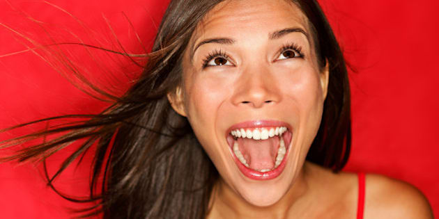 surprised screaming woman looking up at copy space on red background. Beautiful young shocked mixed race Caucasian / Asian female model amazed.
