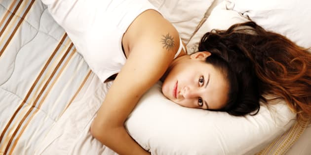 a young woman laying on the bed.