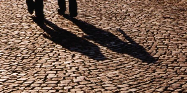 Pedestrian shadows on cobblestones.