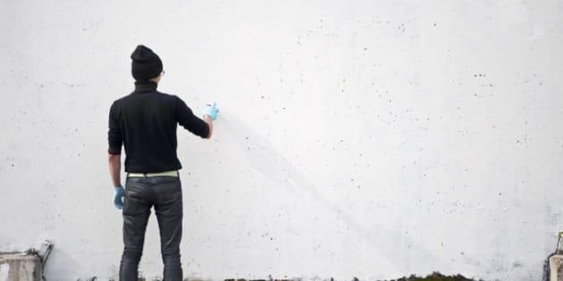 teenager draws on the wall graffiti