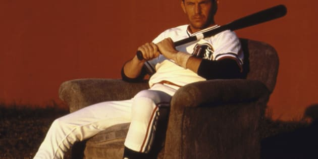 Actor Kevin Costner sitting in an upholstered chair, wearing uniform & holding a bat, during the filming of the movie Bull Durham.  (Photo by Matthew Naythons//Time Life Pictures/Getty Images)