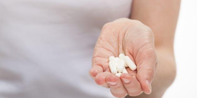 woman hand holding heap of pills