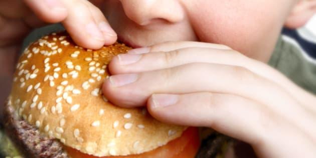 young boy eating cheeseburger