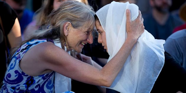 Asha Deliverance, left, the mother of Taliesin Myrddin Namkai-Meche, leans in and embraces a woman who approached her at the May 27 vigil.