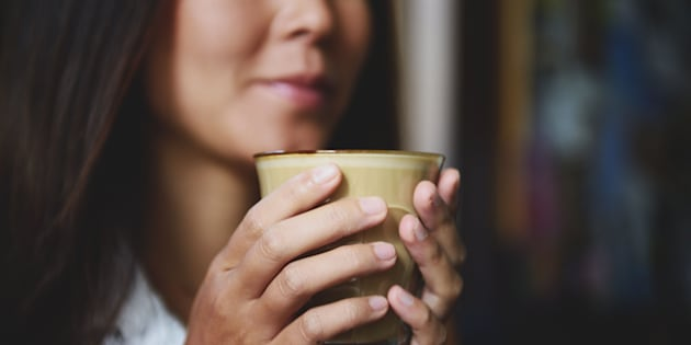 A young woman holds a cup of designer coffee in two hands in a coffee shop.