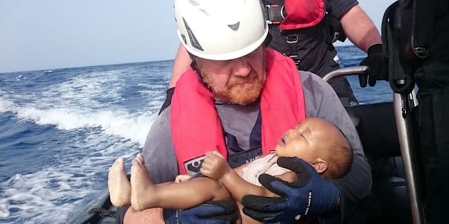 German rescuer from the humanitarian organisation Sea-Watch holds a drowned migrant baby, off the Libyan cost May 27, 2016. The baby, who appears to be no more than a year old, was pulled from the sea after a wooden boat capsized last Friday. (Christian Buettner/Eikon Nord GmbH Germany/Handout via REUTERS)