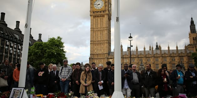 LONDON, UNITED KINGDOM - JUNE 17:  People stand near the tributes and flowers as they attend a vigil in memory of Labour MP Jo Cox in Parliament Square on June 17, 2016 in London, England. The Labour MP for Batley and Spen was about to hold her weekly constituency surgery in Birstall Library yesterday when she was shot and stabbed in the street on June 16. A 52-year old man is being held in Police custody in connection with the death.  (Photo by Dan Kitwood/Getty Images)