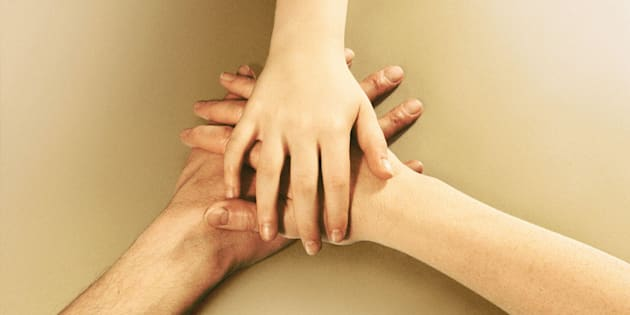 Parents and girl (9-11), hands on top of each other, close-up