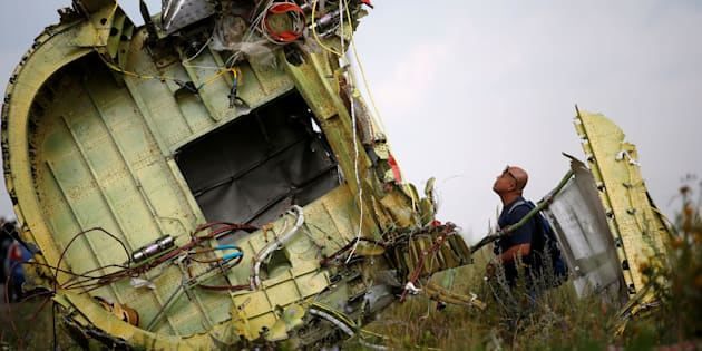 A Malaysian air crash investigator inspects the crash site of Malaysia Airlines Flight MH17, near the village of Hrabove (Grabovo) in Donetsk region, Ukraine, July 22, 2014.  REUTERS/Maxim Zmeyev/File Photo     TPX IMAGES OF THE DAY