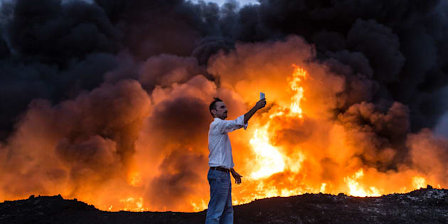 A man takes a selfie in front of oil that has been set ablaze in the Qayyarah area of Iraq, some 35 miles south of Mosul, on Thursday during an Iraqi forces operation against Islamic State militants in the battle for the key city.