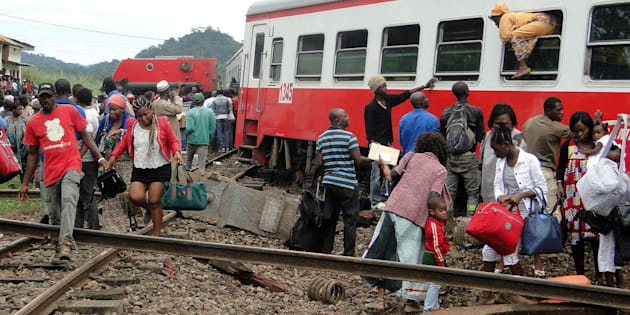 TOPSHOT - A passenger escapes a train car using a window as others leave from the site of a train derailment in Eseka on October 21, 2016.  Fifty-three were killed and over 300 injured when a packed Cameroon passenger train derailed on October 21 while travelling between the capital Yaounde and the economic hub Douala, state broadcaster Crtv said. The train, crammed with people due to road traffic disruption between the two cities, left the tracks just before reaching the central city of Eseka, Transport minister Edgar Alain Mebe Ngo'o said earlier.  / AFP / STRINGER        (Photo credit should read STRINGER/AFP/Getty Images)