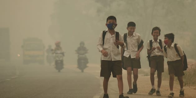 Students walk along a hazy street in Jambi, Indonesia, on Sept. 29, 2015. The World Meteorological Organization reported Monday that carbon concentrations surpassed 400 parts per million last year for the first time.