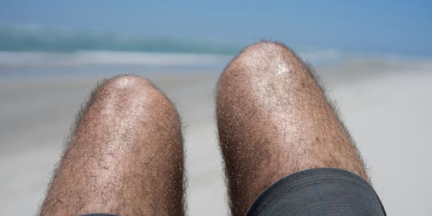 A man with hairy legs and wearing shorts sunbathing with his knees up.