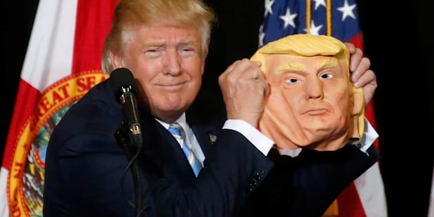 Republican presidential nominee Donald Trump holds up a mask of himself as he speaks during a campaign rally in Sarasota, Florida, U.S. November 7, 2016.   REUTERS/Carlo Allegri