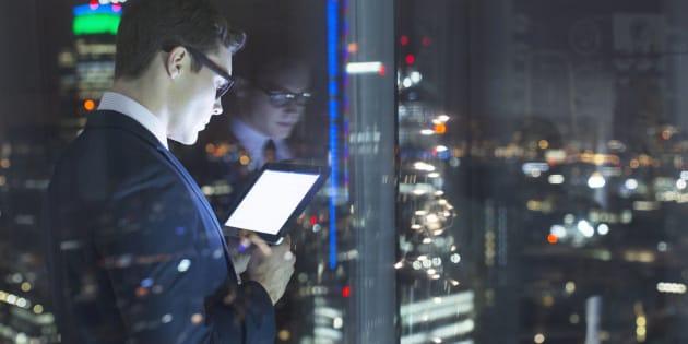 Businessman using digital tablet in urban window at night