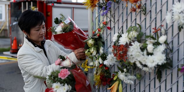 A woman places flowers at a makeshift memorial near the scene of a fire in the Fruitvale district of Oakland, California, Dec.3, 2016.