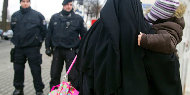BERLIN, GERMANY - JANUARY 13:  A Muslim woman, wearing a burqa, carries a child as she walks past police outside a building where Salafites are holding a benefit rally for Syrian Muslims on January 13, 2013 in Berlin. Two dozen members of 'Pro Deutschland' waited in the centre of Berlin for Salafites who originally planned to hold a public gathering to raise money for Muslims in Syria, which included prominent speakers such as radical Islamic preacher Pierre Vogel. They then moved the event to a private gathering in Neukoelln district. Salafites are an ultra-conservative group of Muslim sunnis with hundreds of members in Berlin and the area around Bonn and cologne. German authorities are keeping a close eye on the group, espacially since clashes that broke out last year in which Salafite demonstrators attacked police and right-wing counter-demonstrators. on January 13, 2013 in Berlin, Germany.  (Photo by Target Presse Agentur Gmbh/Getty Images)
