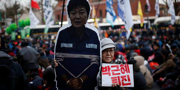 A woman poses for photographs with a cutout of South Korean Park Geun-hye as they march toward the Presidential Blue House during a protest calling for South Korean President Park Geun-hye to step down in central Seoul, South Korea, December 3, 2016.  REUTERS/Kim Hong-Ji