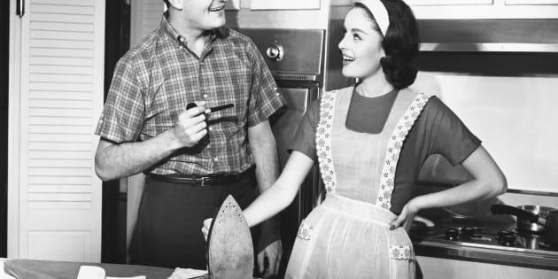 UNITED STATES - CIRCA 1950s:  Couple ironing.