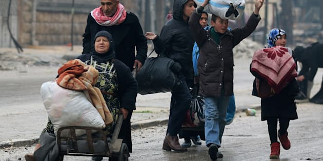 A man pushes a woman on a cart as they flee deeper with others into the remaining rebel-held areas of Aleppo, Syria December 13, 2016. REUTERS/Abdalrhman Ismail