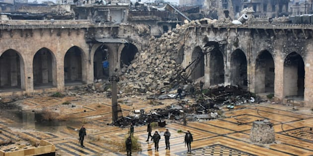 TOPSHOT - A general view shows Syrian pro-government forces walking in the ancient Umayyad mosque in the old city of Aleppo on December 13, 2016, after they captured the area. After weeks of heavy fighting, regime forces were poised to take full control of Aleppo, dealing the biggest blow to Syria's rebellion in more than five years of civil war.   / AFP / George OURFALIAN        (Photo credit should read GEORGE OURFALIAN/AFP/Getty Images)