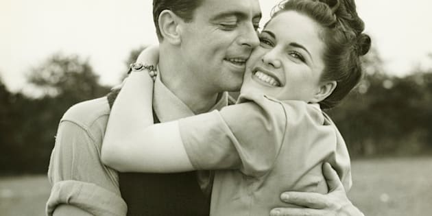 Young couple embracing in field, man kissing woman, (B&W)