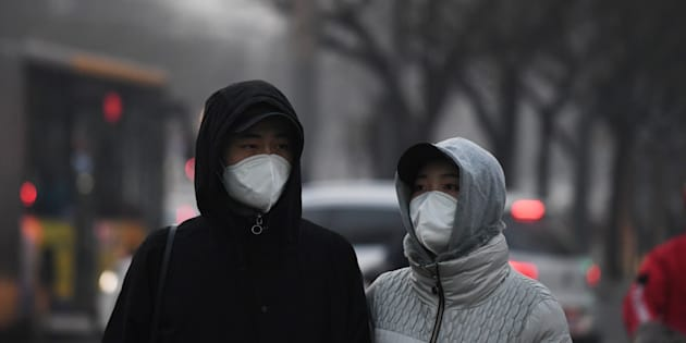 Pedestrians wear masks to protect themselves from pollution in Beijing on December 19, 2016.  Hospital visits spiked, roads were closed and flights cancelled on December 19 as China choked under a vast cloud of toxic smog, with forecasters warning worse was yet to come. At least 23 cities in the world's most populous nation have issued red alerts for air pollution since December 16, according to the official Xinhua news agency. / AFP / GREG BAKER        (Photo credit should read GREG BAKER/AFP/Getty Images)