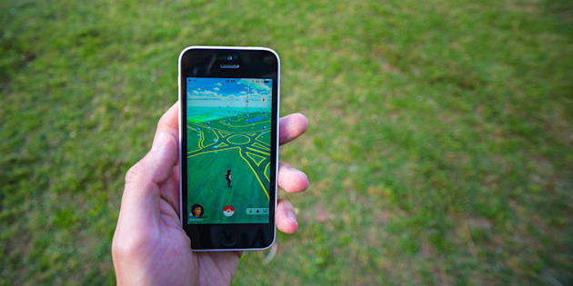 Buenos Aires, Argentina - November 11, 2016: Apple iPhone 5c held in one hand showing its screen with Pokemon Go application. Grass on the background.